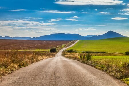 Road around fields through rural landscape in sunny summer day. Rajec Valley area, Slovakia, Europe.