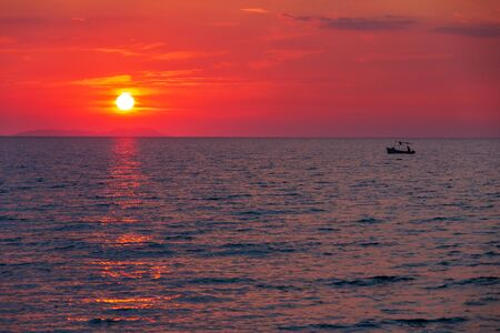 Boat with a fisherman on calm sea at sunset near the island of Corfu, Greece, Europe. Stockfoto