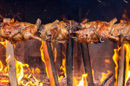 Roasting chicken on an open fire in the market.