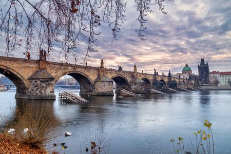 Charles Bridge and historical buildings of old town on Vltava riverbank in Prague at sunrise, Czech Republic, Europe.
