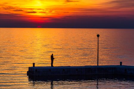 Sunset with silhouette of fisherman at sea. The Green lagoon in Porec at Istria peninsula, Croatia, Europe.