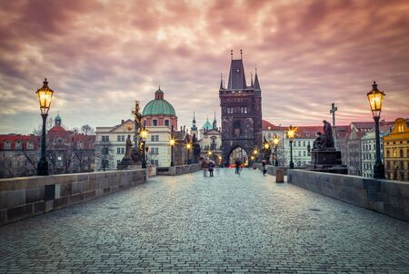 Charles Bridge with lit lamps in the early morning. Prague, the capital of the Czech Republic, Europe.