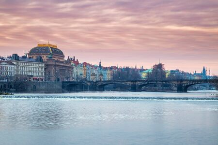 Historic buildings with the National Theater on the Vltava river bank at sunrise in Prague, Czech Republic, Europe.