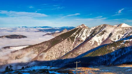 Winter mountain landscape at a sunny day with fog in the valleys. The Mala Fatra national park in Slovakia, Europe.