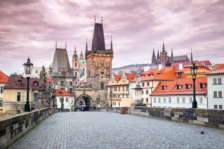 Lesser Town Bridge Tower at Charles Bridge in Prague with castle on background at sunrise, Czech Republic, Europe.