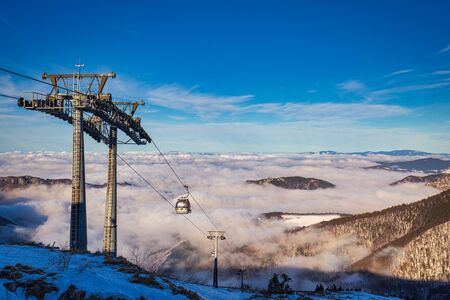 Winter mountain landscape at a sunny day with fog in the valleys.  Cable car lift in The Mala Fatra national park in Slovakia, Europe. Stockfoto