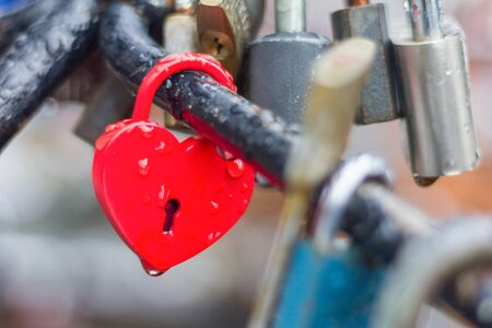 Heart-shaped love padlock with drops of rain in close-up view.