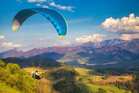 Vol en parapente depuis la colline de Stranik au-dessus du paysage montagneux du bassin de Zilina au nord de la Slovaquie. Parc national de Mala Fatra en arrière-plan, Slovaquie, Europe. Banque d'images
