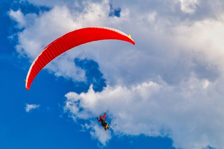 Flying paraglider on a background of blue sky with clouds.