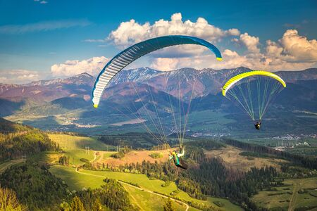 Flying paragliders from the Stranik hill over the mountainous landscape of the Zilina basin in the north of Slovakia. Mala Fatra National Park in the background, Slovakia, Europe.