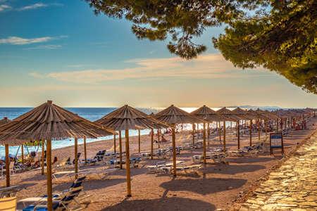 Beach with straw umbrellas at sunset near Primosten town, a popular tourist destination on the Dalmatian coast of Adriatic sea in Croatia, Europe.