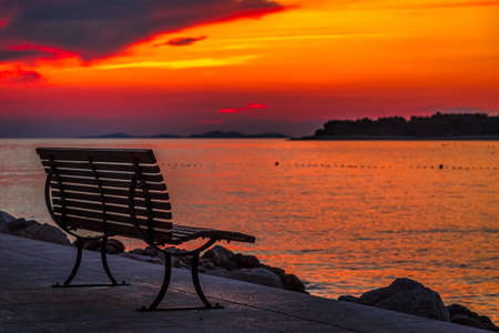 Sea landscape at sunset with bench in Primosten town, a popular tourist destination on the Dalmatian coast of Adriatic sea in Croatia, Europe.