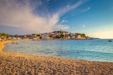 Beach at sunset near Primosten town, a popular tourist destination on the Dalmatian coast of Adriatic sea in Croatia, Europe. Stock Photo