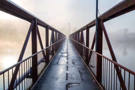 Iron bridge for pedestrians over the river in a misty morning.