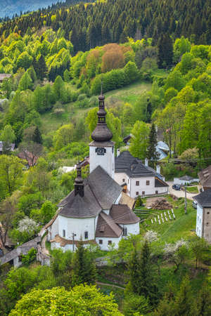 Church in The Spania Dolina village with surrounding landscape, Slovakia, Europe.