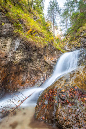 Waterfall on wild stream in a forest at autumn. The Vratna valley in Mala Fatra national park, Slovakia, Europe.