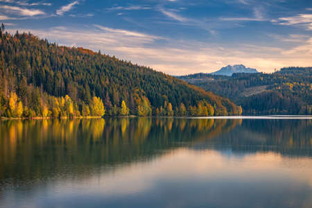 Autumn landscape with mountains on background. Mirroring of colorful forests on the water surface of the lake.