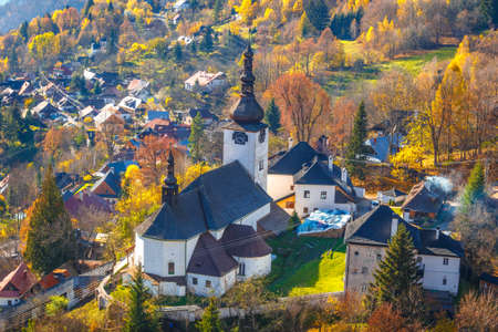 The Spania Dolina village with church and historic buildings in valley of autumn landscape, Slovakia, Europe.