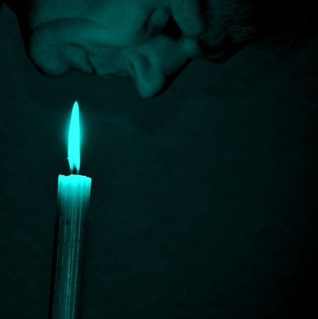 man face: old man face with green effect looking at burning candle