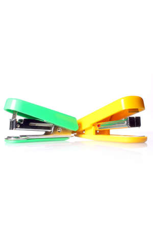 Stationery - two staples yellow and green on a white background photo