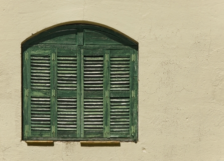 window shutters on yellow wall