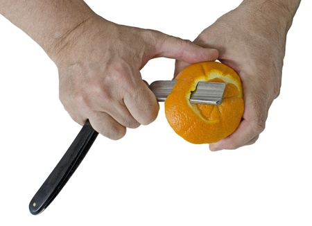 Peeling an orange with a razor  Isolated on white background