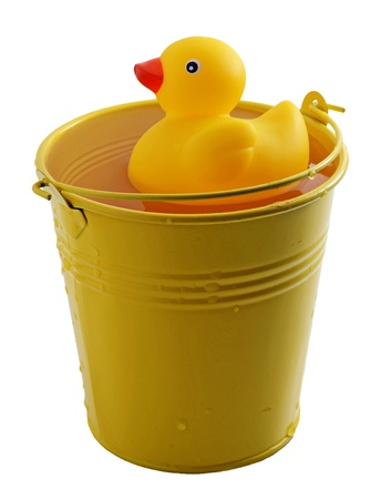 Rubber duck taking a bath into a yelow bucket  Isolated on white background Stock Photo