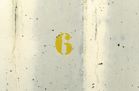 The number six yellow painted on a concrete wall