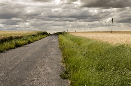 Rural road through cultivated fields, with parallel telegraph line  Cloudy Stock Photo