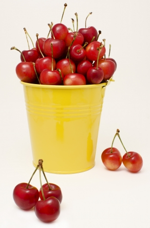 Yellow small bucket filled with cherries