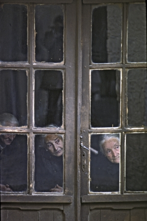Three old women seen through the window of his house, what happens on the street of a Castilian village on May, 1978, in Covarrubias, Spain  Editorial