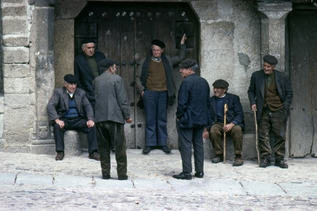 A group of elders talk in the arcades of the square of the medieval village located in the Sierra de France  on August, 1979 in La Alberca (Salamanca), Spain Editorial