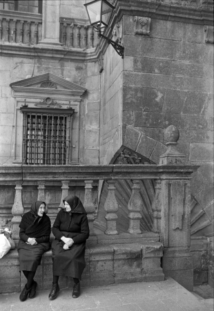 Two elderly women, dressed in a traditional way, seated converse near the Gothic Cathedral on August, 1977 in Santiago de Compostela, Galicia, Spain. Black and white