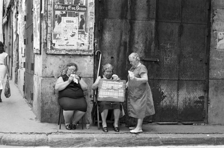 An old woman buys a traditional Spanish lottery to a blind woman who eats a sandwich on August, 1982 in Valencia, Spain. Black and white
