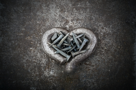 A steel heart is full of nails on a metal background
