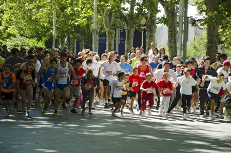 A larger number of runners all ages break from the starting line at the beginning of the popular race during the celebration of the fair and festivities of the Virgen of San Lorenzo on September 2, 2012 in Valladolid, Spain Stock Photo - 15108651