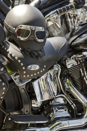 Black motorcycles with black leather seats and helmet and chrome parts photo