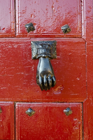 A decorative iron hand as a door knocker over a red door photo