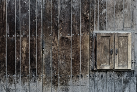 Old neglected rustic shutters closed on aging wooden wall photo
