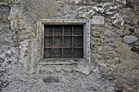 A old barred window in a stone wall photo