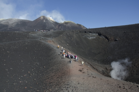 view of some people along one of the craters of Mount Etna photo