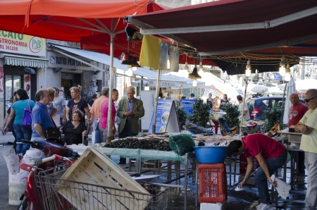 PALERMO, SICILY, ITALY - OCTOBER 3, 2012: Unidentified buyers and sellers in a street market of fish, on October 3, 2012 in Palermo, Italy Stock Photo - 15877083