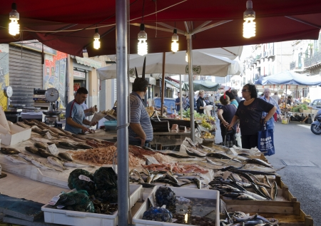 PALERMO, SICILY, ITALY - OCTOBER 3, 2012: An unidentified middle-aged woman, buy fish at a street stall, on October 3, 2012 in Palermo, Italy Stock Photo - 15877067