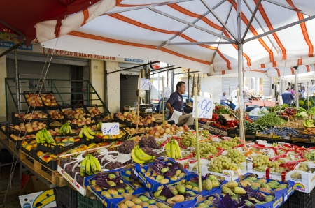 PALERMO, SICILY, ITALY - OCTOBER 3, 2012: A unidentified men, selling their goods (fruit) at a traditional sales stall, on October 3, 2012 in Palermo, Italy