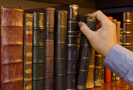 Image of a hand selecting a old book from a bookshelf