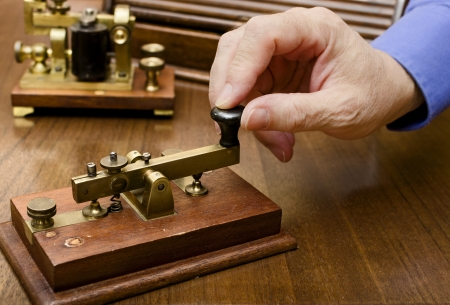 A hand manipulating an old morse transmitter Stock Photo