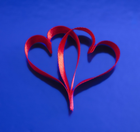 Two red ribbon in heart shape over blue background Stock Photo - 16875734