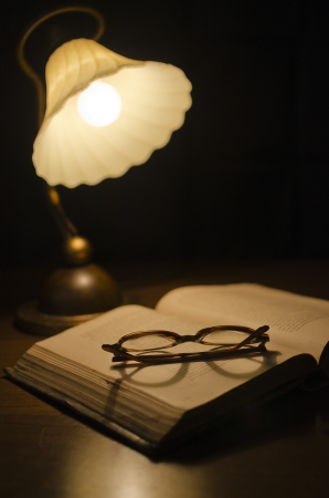 open book   glasses under lamp  selective focus on the glasses, the book photo