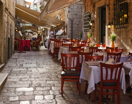 DUBROVNIK, CROATIA - MAY 15, 2013: tables of a street restaurant in the old town of Dubrovnik. On 15 May 2013 in Dubrovnik, Croatia Editorial