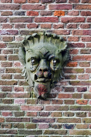 stone face on a brick wall. Holland Stock Photo - 23432170
